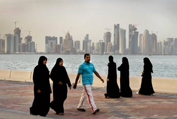 People walk by the sea in Doha, Qatar, in 2012.