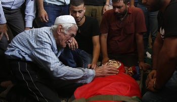 A relative of Palestinian Bara Hamamdah, who was shot dead during clashes with Israeli forces, cries over his body during his funeral in the Dheisheh Refugee Camp, near the West Bank town of Bethlehem, on July 14, 2017