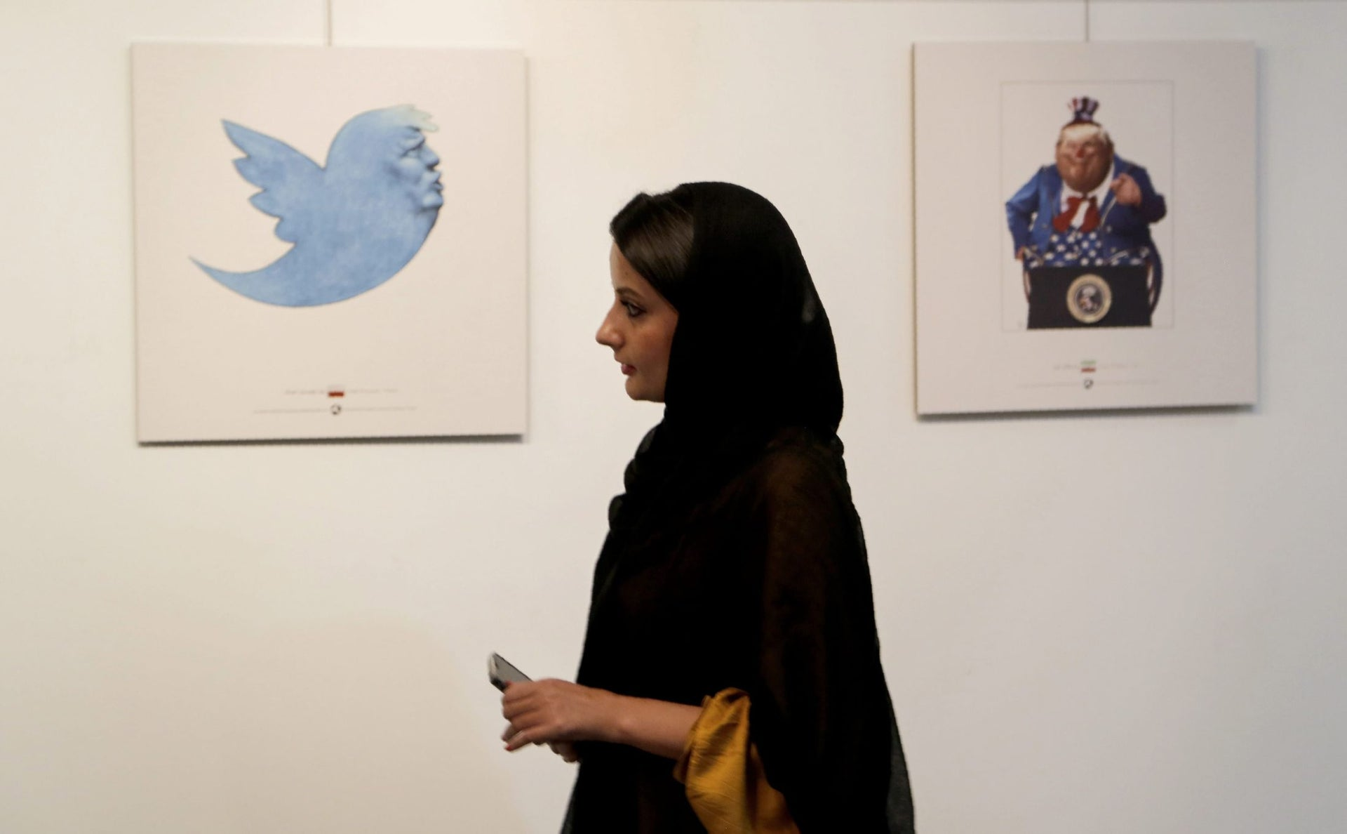 An Iranian woman looks at cartoons of US President Donald J. Trump at an exhibition of the Islamic Republic's 2017 International Trumpism cartoon and caricature contest, in the capital Tehran on July 3, 2017.