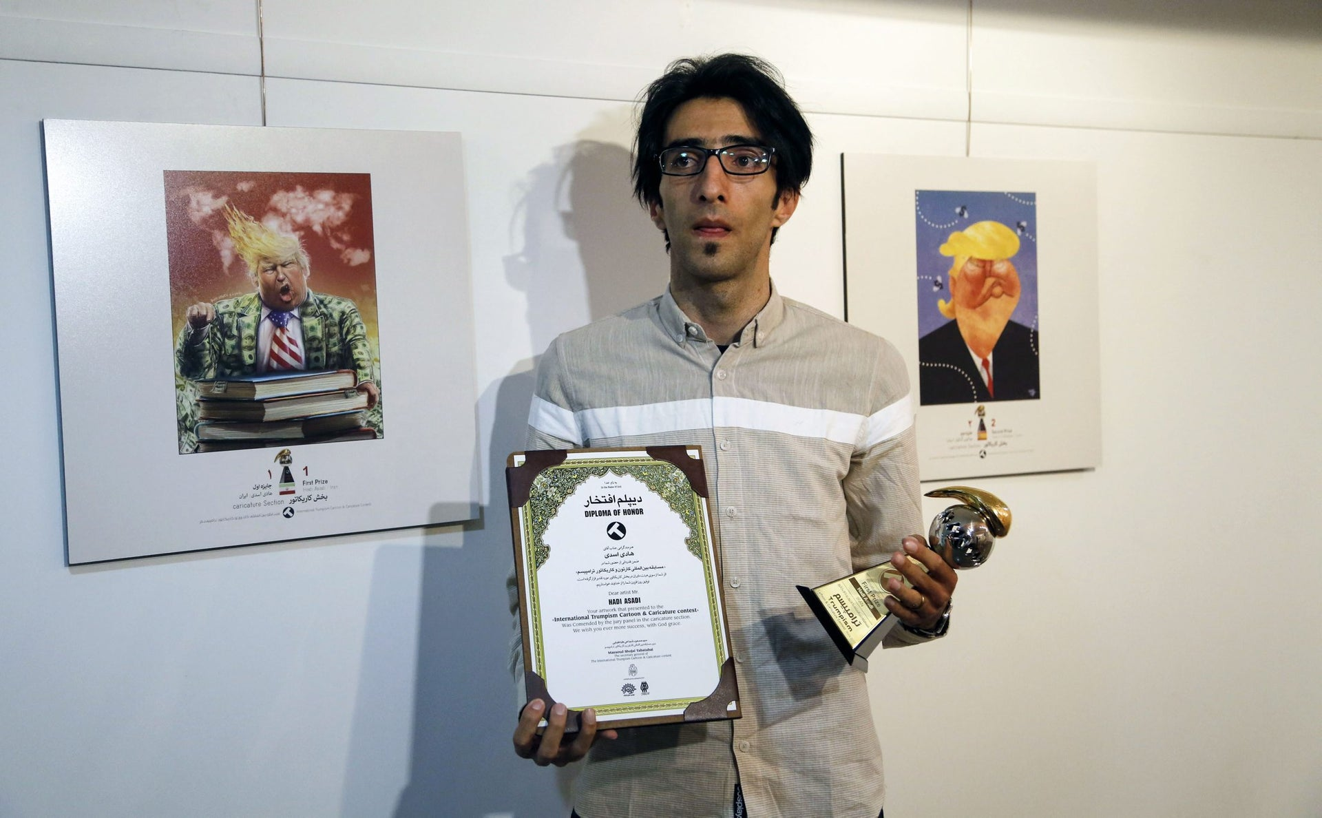 Iranian cartoonist Hadi Asadi poses for a picture with a trophy and an award next to cartoons of US President Donald J. Trump, at an exhibition of the Islamic Republic's 2017 International Trumpism cartoon and caricature contest, in the capital Tehran on July 3, 2017.