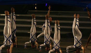 Gymnasts wearing costumes with a Star of David design do handstands in the closing ceremony of a previous Maccabiah Games.