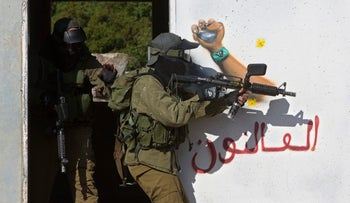 Israeli soldiers train with paintball guns in a base designed to look like a Lebanese village in preparation for potential conflict with Hezbollah, March 2017.