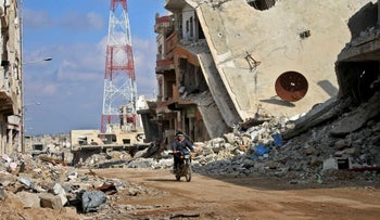 A man rides his motorcycle past damaged buildings in the southwestern city of Daraa, Syria, March 16, 2017.