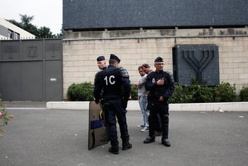 Police officers guard the Sarcelles synagogue, after a pro-Palestinian protestors set fire to cars, pillaged stores and attacked two synagogues. July 21, 2014