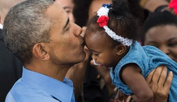 U.S. President Barack Obama holds up a baby after speaking in Kissimmee, Florida, November 6, 2016 as he campaigns for Democratic presidential nominee Hillary Clinton during a Hillary for America campaign event.