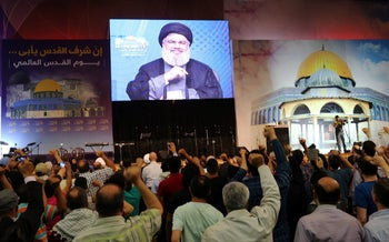Hezbollah leader Hassan Nasrallah addresses supporters onscreen during a rally marking Al-Quds day in Beirut's southern suburbs, Lebanon. June 23, 2017