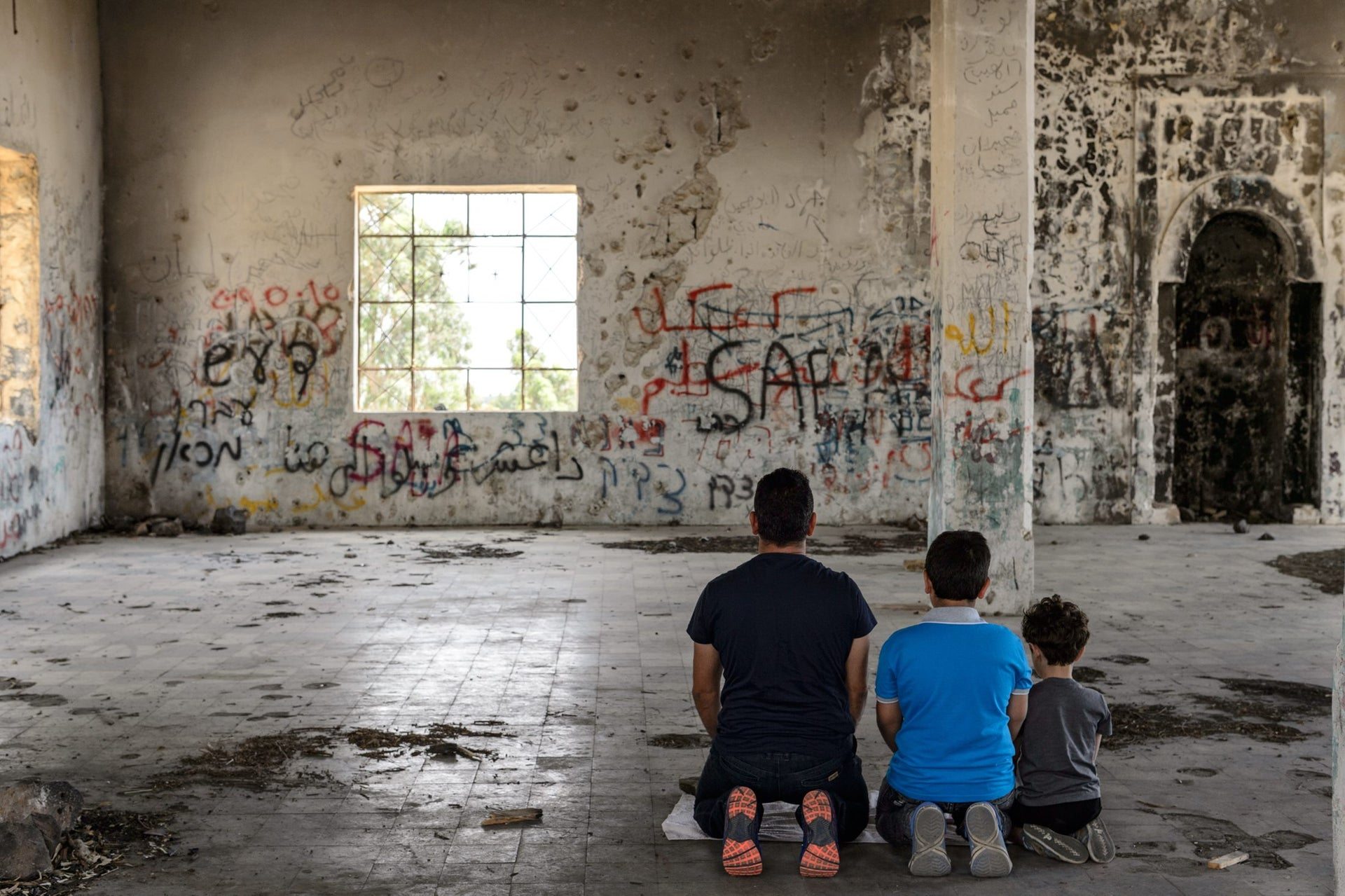 A man and two boys pray in the abandoned mosque at Hushniya, Golan Heights, 2017.