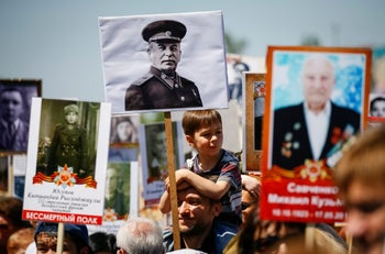 A man holding a portrait of Soviet leader Joseph Stalin during a Victory Day parade in Almaty, Kazakhstan, May 9, 2017.