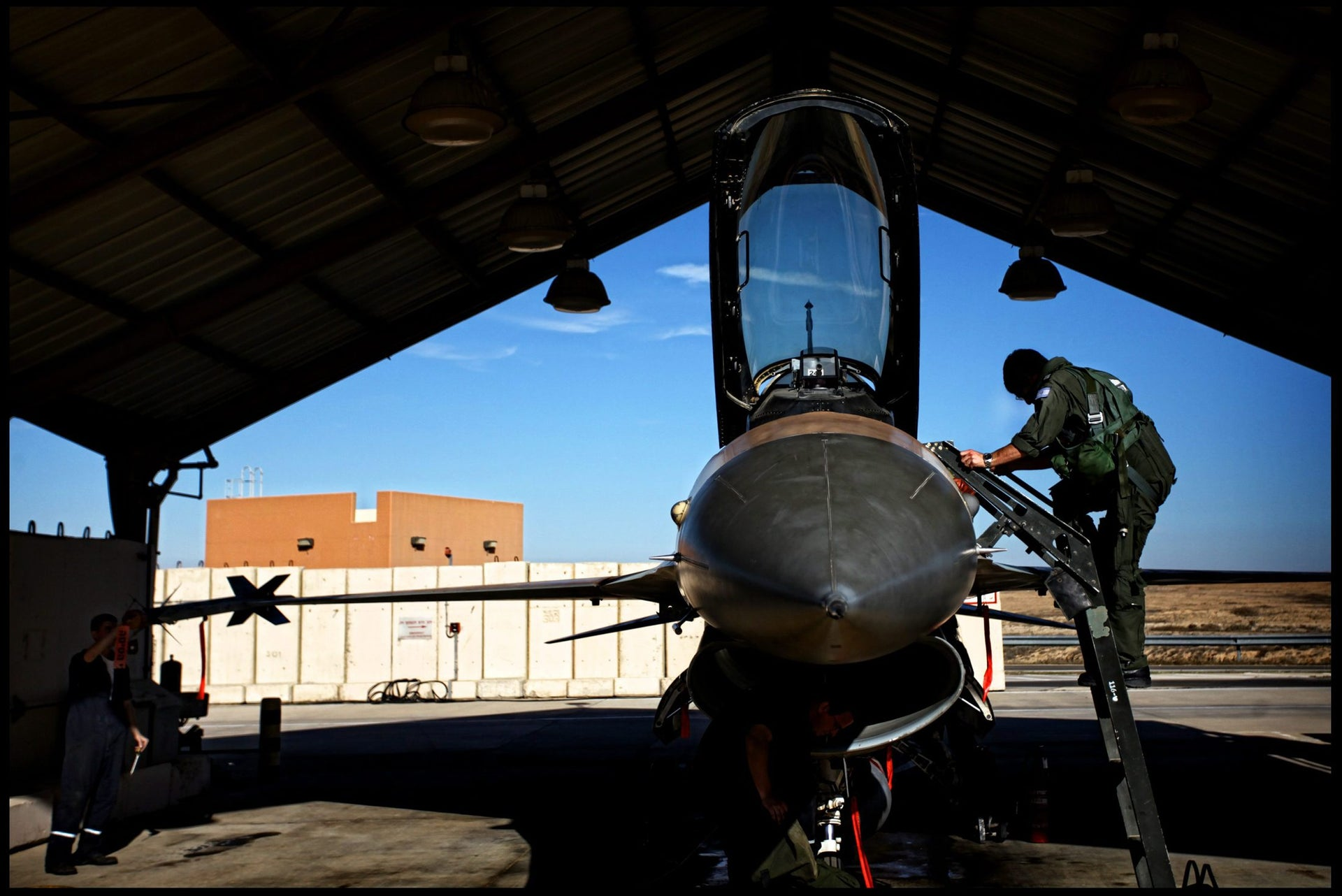 """A pilot climbs into an F-16 """"Netz"""" (Hawk) fighter plane at the Israel Air Force's Nevatim base in 2011."""