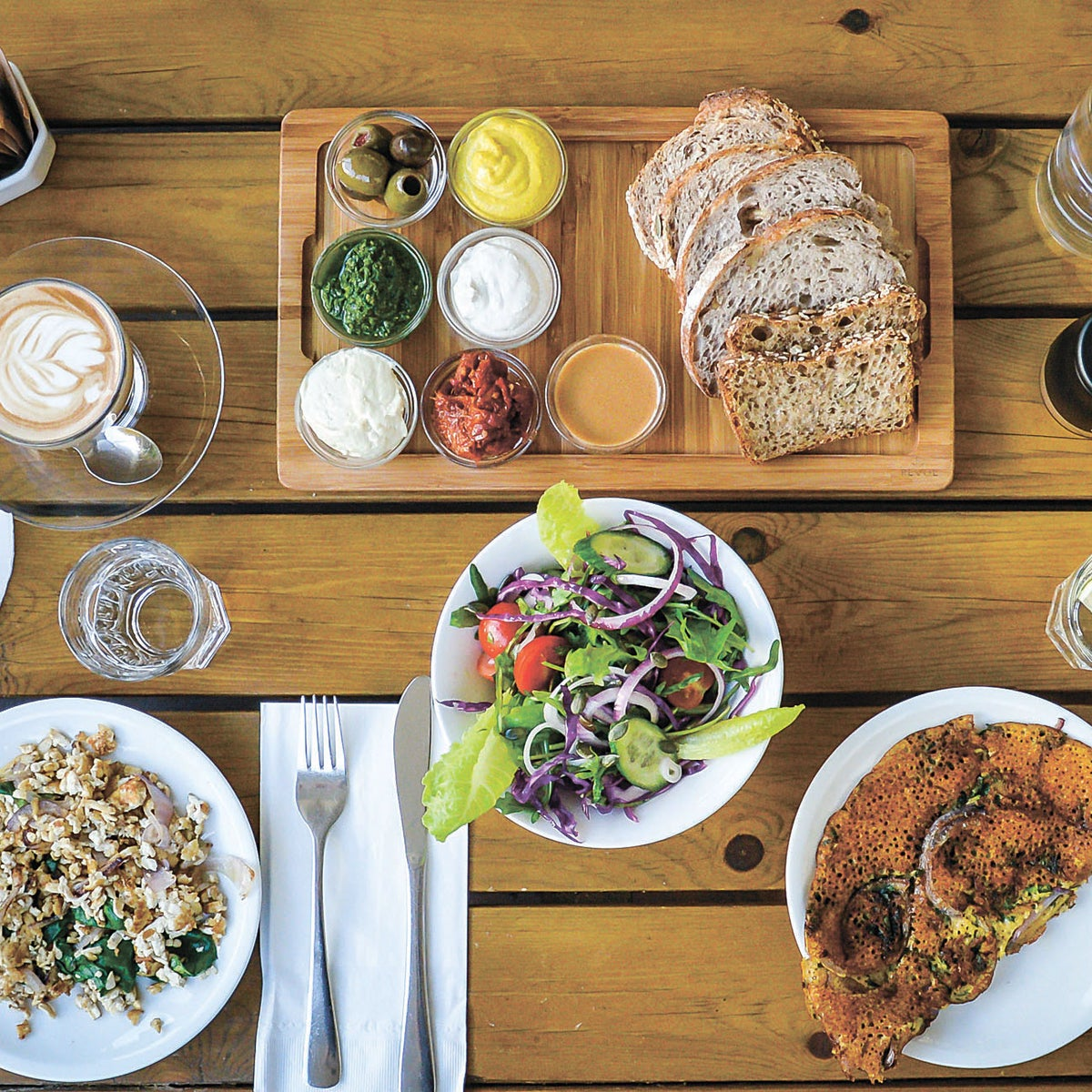 Anastasia café serves a rich breakfast with bread, dips, spreads, salad, a hummus flour omelet and drinks.