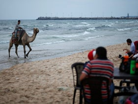 A Palestinian man rides a camel as people sit on a beach on a hot day in Gaza City July 12, 2017.