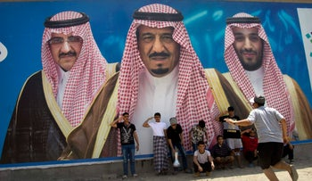 Saudi boys pose in front of a huge billboard showing King Salman (center), his son Mohammed bin Salman (right), and Prince Mohammed bin Nayef (left) in Taif, Saudi Arabia on April 4, 2017.