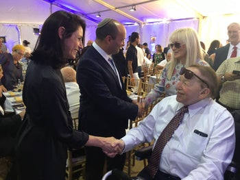 Naftali Bennett, center, shakes hands with Miriam Adelson, with Sheldon Adelson sitting at right at the cornerstone laying for Ariel University's medical school, June 2017.