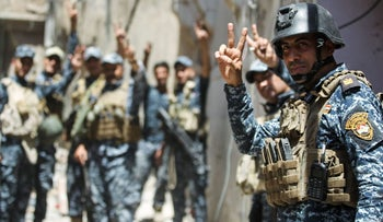 Members of the Iraqi police raise the victory hand gesture as they recapture Mosul from ISIS insurgents.