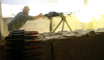 A Kurdish fighter from the People's Protection Units (YPG) fires heavy machine-gun at Islamic State militants in Raqqa, Syria June 21, 2017.