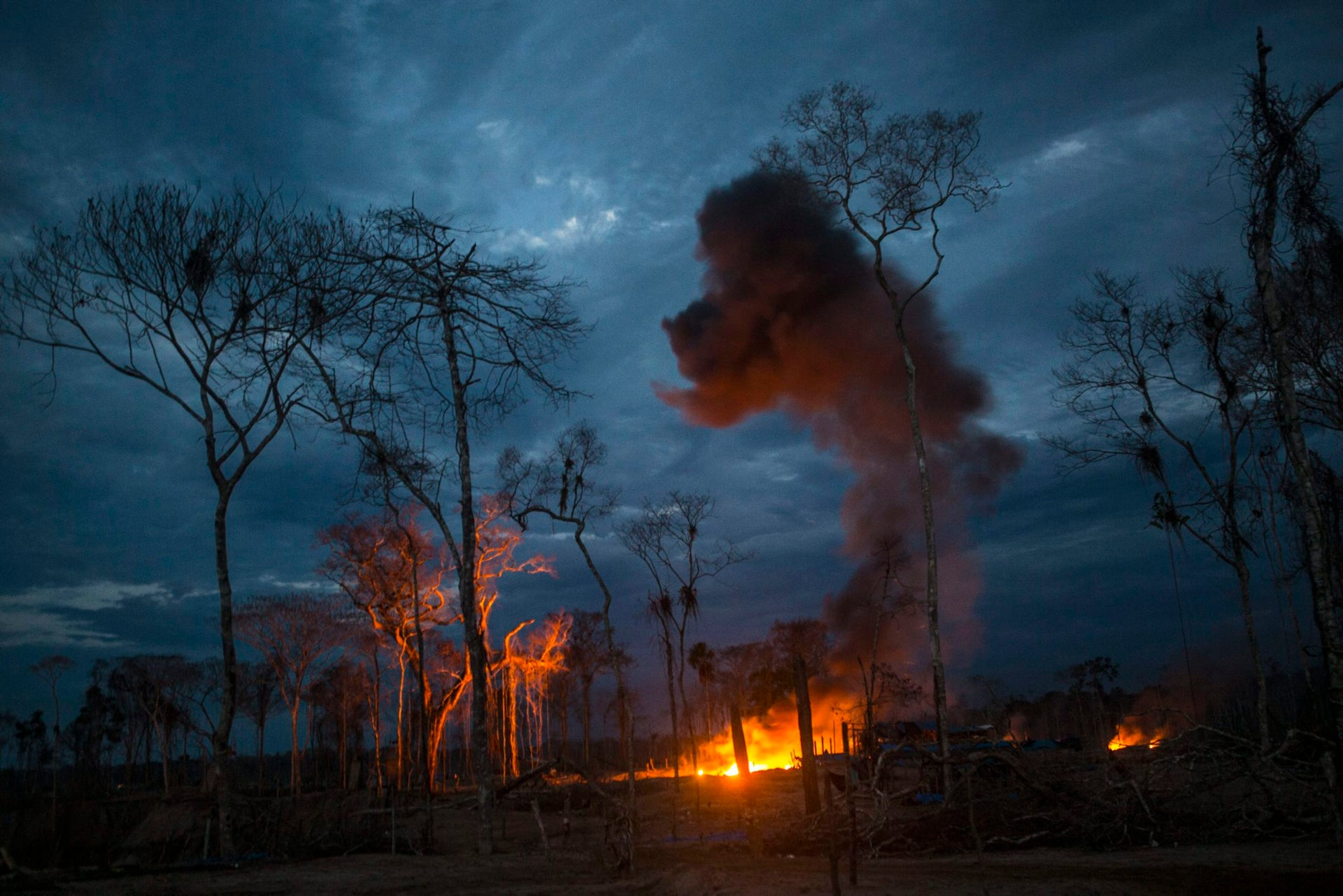 Police torch motorcycles, generators and other supplies in a raid on an illegal gold mining camp inside the Amazonian National Reserve buffering zone of Tambopata in Puerto Maldonado, Peru, Aug. 2015.