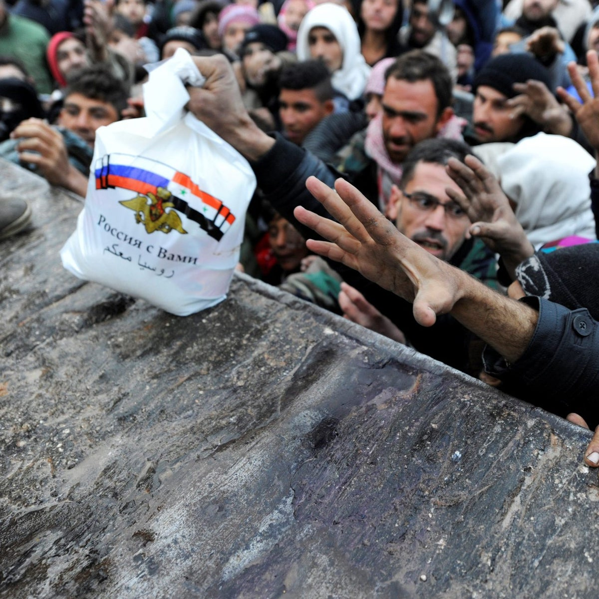 Syrians who have been evacuated from eastern Aleppo, reach out for Russian food aid in government-controlled Jibreen area in Aleppo, Syria November 30, 2016.