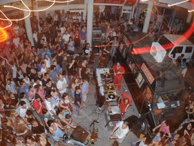 A live performance at Teder. A large crowd gathers in front of a DJ stand in the courtyard of Beit Romano.