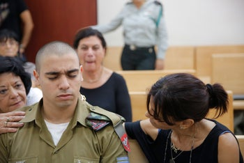 Israel Defense Forces soldier Elor Azaria, the so-called Hebron shooter, with his mother in the courtroom in Jaffa, on Aug. 30, 2016.