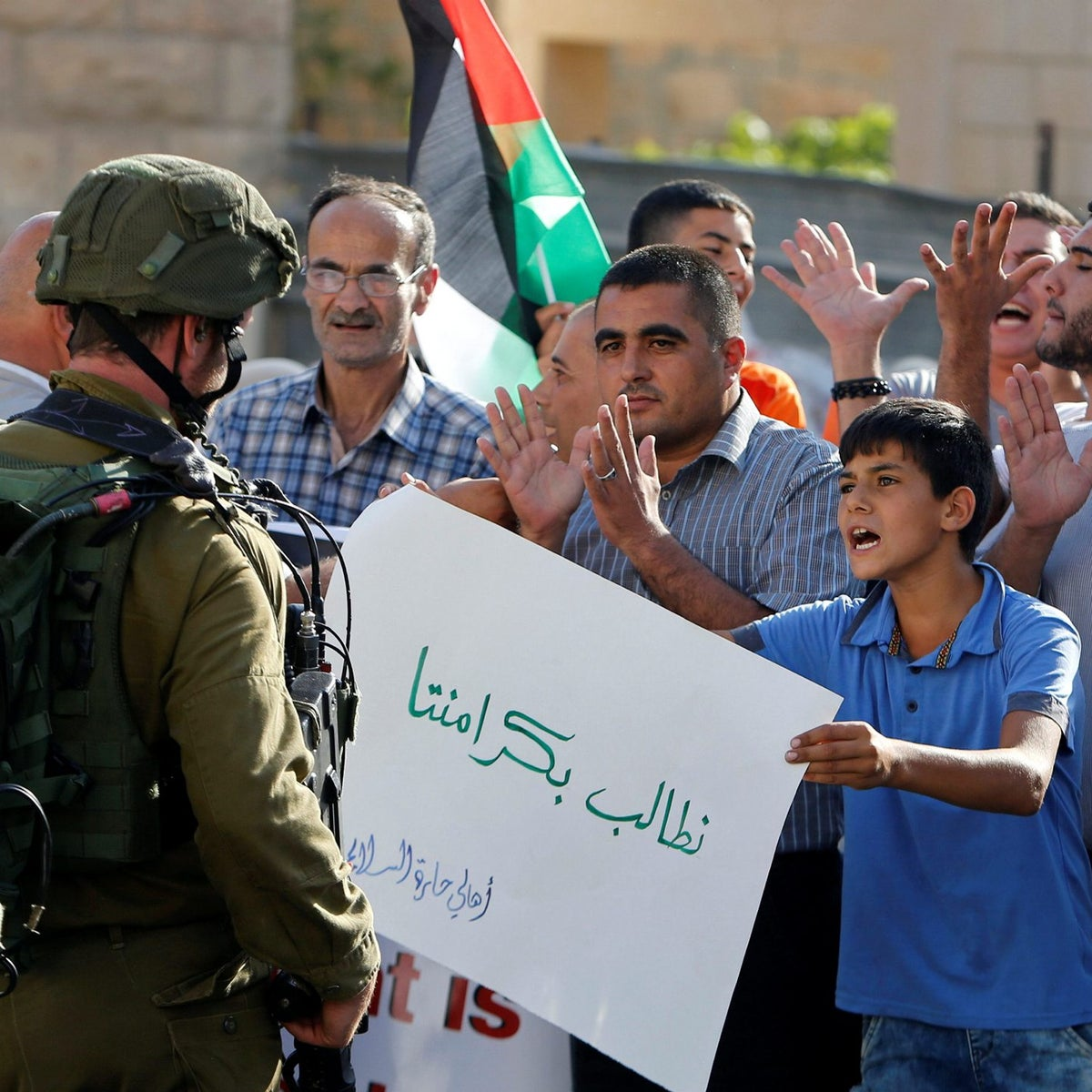 A Palestinian boy holds a sign that reads 'we demand our dignity' in front of Israeli soldiers during a protest calling for the reopening of a closed street in the West Bank city of Hebron August 24, 2016.