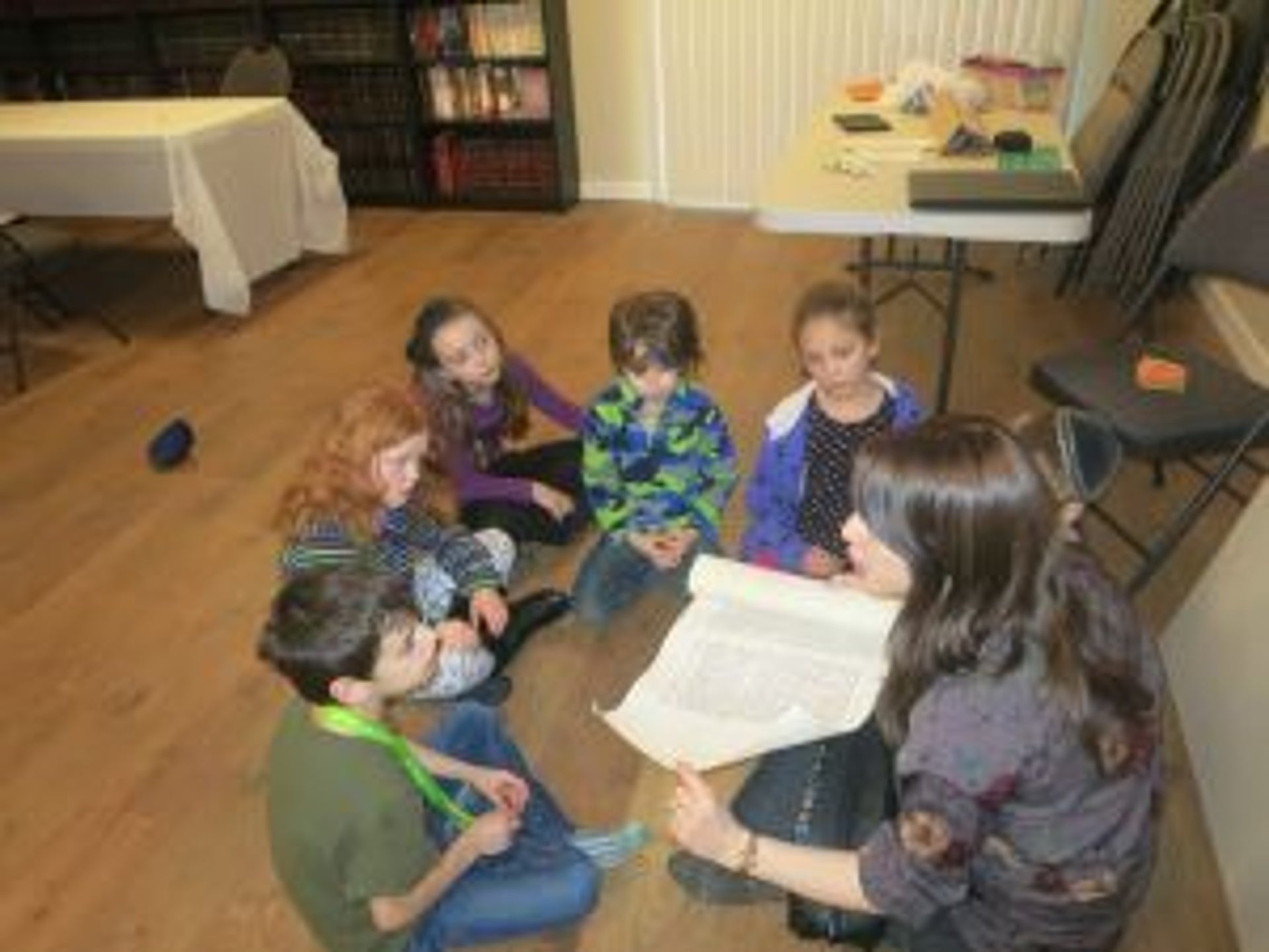 A Hebrew-school class in Nanaimo, British Columbia. Five young children sit on the floor in a circle facing a teacher, also sitting on the floor, who holds a scrolled, printed paper in her hands.