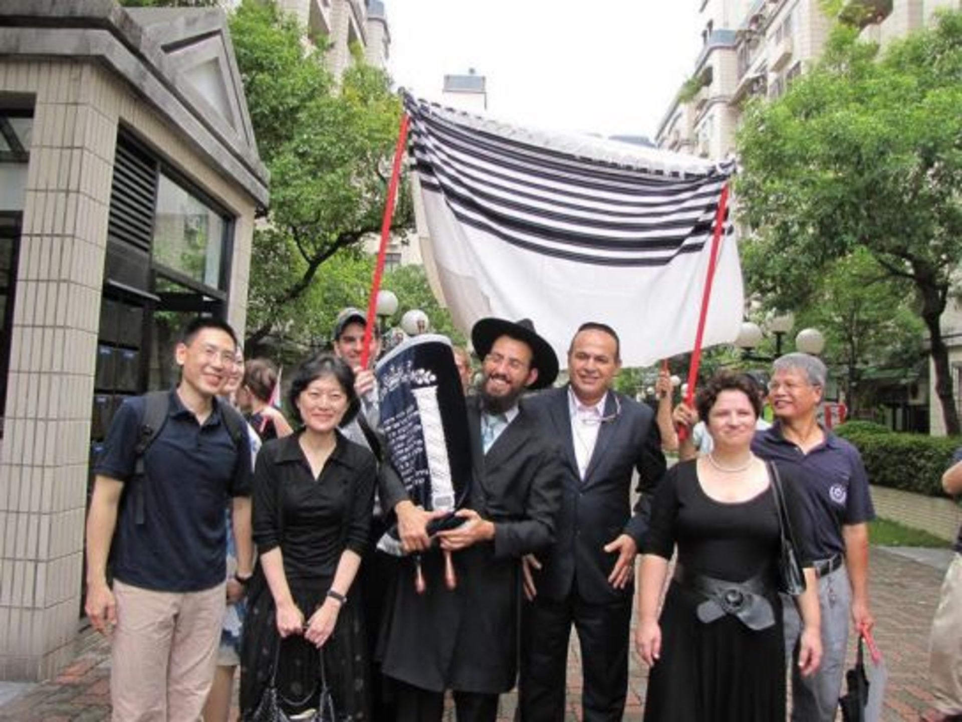 Members of Taiwan's Jewish community, with Rabbi Shlomi Tabib holding the Torah, at a procession for the dedication of a new Torah scroll. A tallit is held above the rabbi and the Torah, as if to form a wedding huppah.