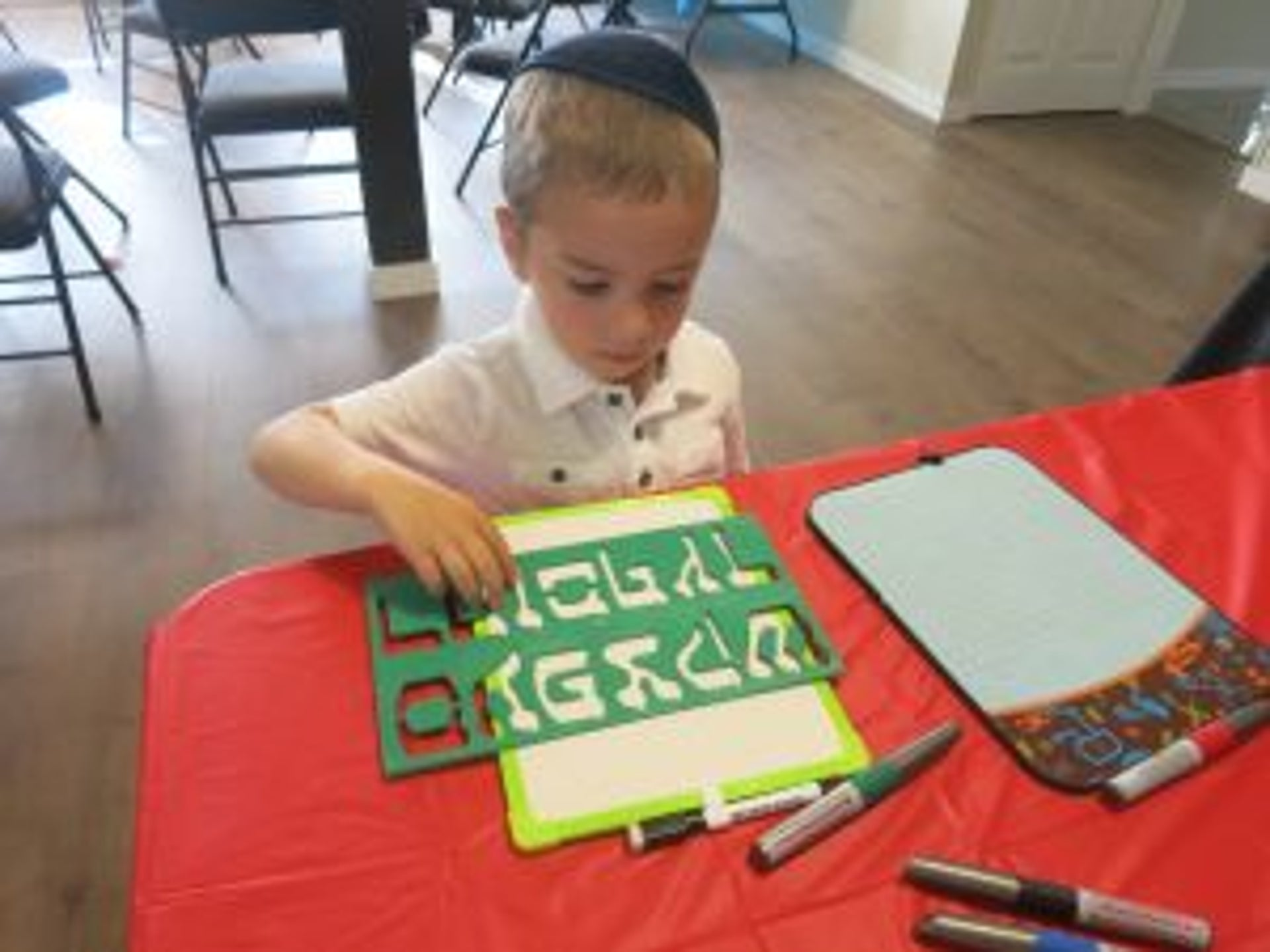 A Hebrew-school class in Nanaimo, British Columbia. A young boy uses a stencil to draw Hebrew letters.