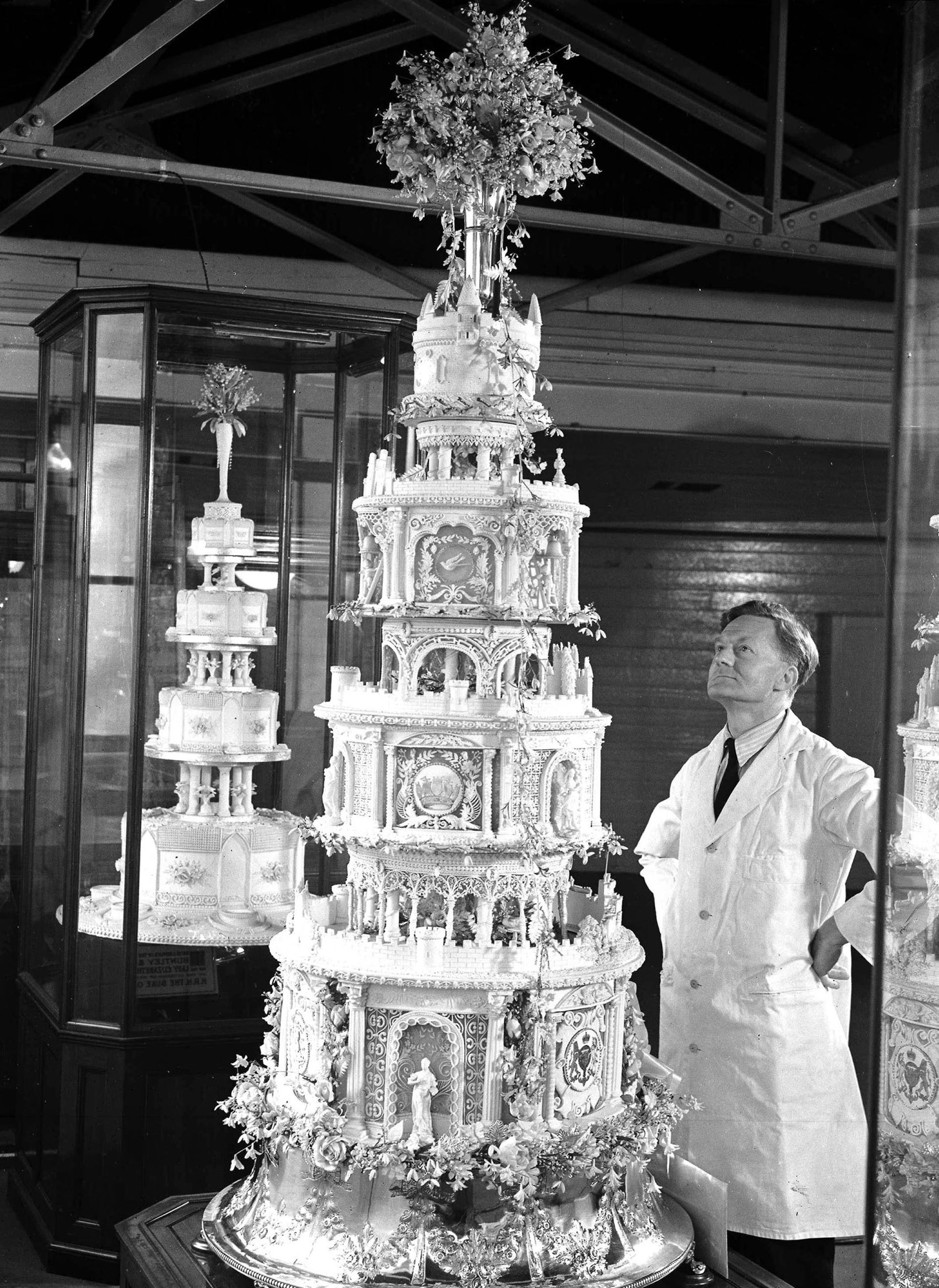 A cake architect working on Princess Elizabeth's wedding cake pictured looking at a replica of the Queen's (later known as the Queen Mother's) cake in Berkshire, 1947.