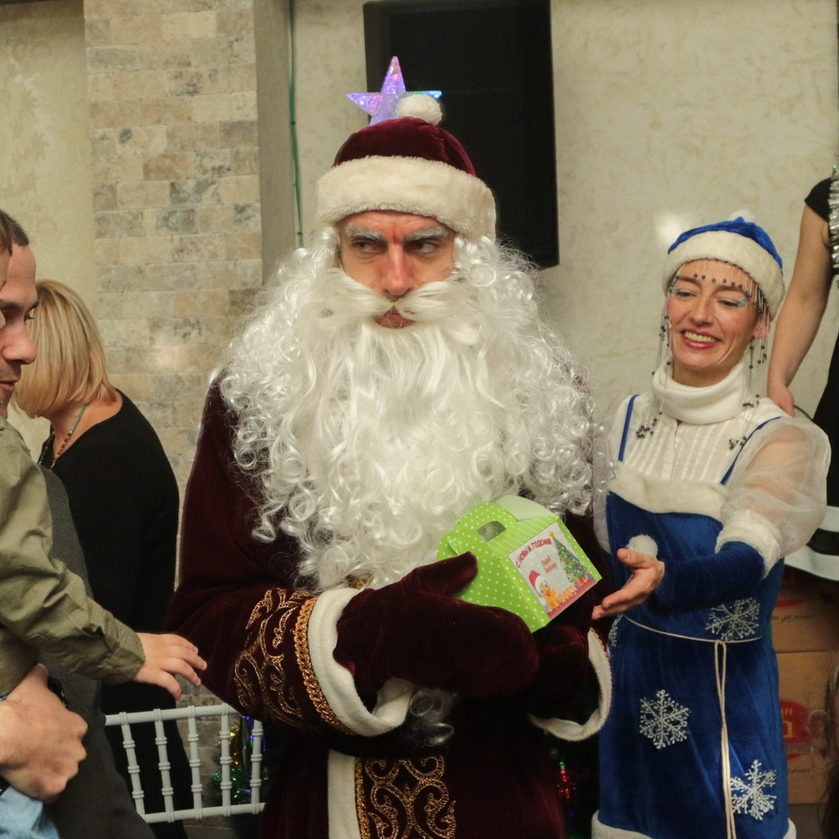 Ariel Krizhopolsk as Grandfather Frost hands out presents to children at a Novy God party in Hadera, December 24, 2016.