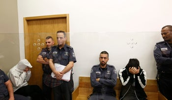 Shiri Sobol and David Eran at their arraignment in Tel Aviv District Court on Thursday. In the picture, each of the suspects sits on a wooden bench, hands covering their faces. Guards stand nearby and the two are on separate benches.