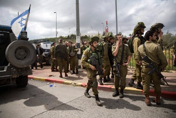 IDF troops guard the site where a woman soldier was stabbed and wounded and her 2 Palestinian assailants shot and killed, near the settlement of Ariel, on March 17, 2016.