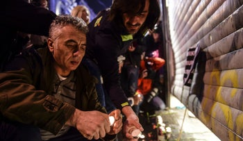 People light candles at the site of a blast on Istiklal Street in central Istanbul on March 19, 2016.