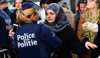 A Police officer pats down a woman before entering the square where people take part in a candlelight vigil to the victims of the Paris attacks, Molenbeek, Belgium, November 18, 2015.