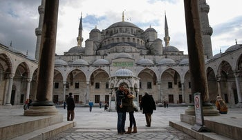 Tourists visit the Sultan Ahmed Mosque, better known as the Blue Mosque, near the site of Tuesday's explosion, in the historic Sultanahmet district in Istanbul, Thursday, Jan. 14, 2016.