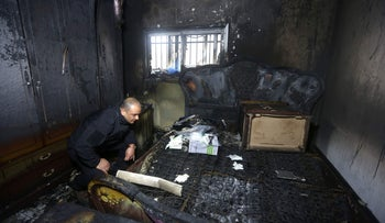 Palestinian police member inspects the damage inside a burnt-out house belonging to a key witness to an arson attack which took place last year by Jewish extremists that killed a Palestinian family, in the Israeli occupied West Bank village of Duma, after fire broke out in the home in the early hours of March 20, 2016.