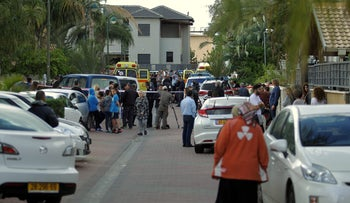 People gather outside Moshav Zeitan home where a murder-suicide took place, March 20, 2016.