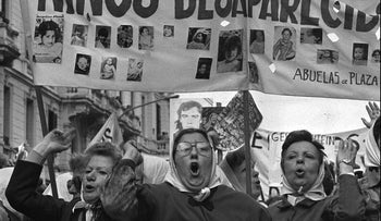 """A demonstration against Argentina's military junta in 1979. Women from Mothers of the Plaza hold up banners. The one that is clearly visible in the photograph has pictures of some of the """"disappeared."""""""
