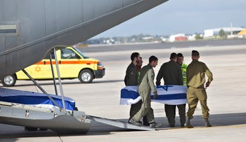 Israeli soldiers carry caskets containing the bodies of three Israelis killed in a terror attack in Istanbul, Turkey, as they arrive in Israel, March 20, 2016.