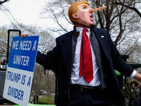 A man dressed up as Donald Trump holds a banner during a protest rally against Republican presidential front-runner Donald Trump in New York on March 19,2016.