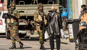 Women speak to soldiers as they block the access to road close to Maalbeek metro station in Brussels on after a series of apparently coordinated explosions ripped through Brussels, March 22, 2016.