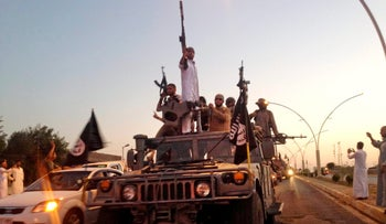 ISIS fighters parade in a commandeered Iraqi security forces armored vehicle down a main road at the northern city of Mosul, Iraq, June 23, 2014.