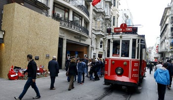 A vintage tram moves past the scene of the suicide bombing at Istiklal Street, a major shopping and tourist district, in central Istanbul, March 22, 2016.