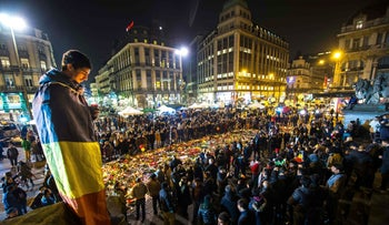 A man wrapped in a Belgian flag holds a candle as people gather at a makeshift memorial in front of Brussel's Stock Exchange on Place de la Bourse (Beursplein) on March 24, 2016,