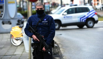 A police officer patrols near a tramway train after it was evacuated during an anti-terrorist operation in the Schaerbeek - Schaarbeel district in Brussels on March 25, 2016.