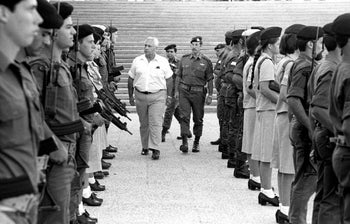 Israeli Defense Minister Ariel Sharon (L) inspects the honor guard during a visit to the central command military base in this picture taken on October 30, 1981 .