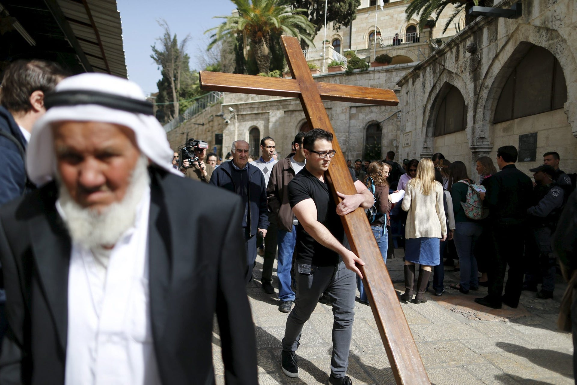 A worshipper carries a cross during a Good Friday procession through the Via Dolorosa in Jerusalem's Old City March 25, 2016.
