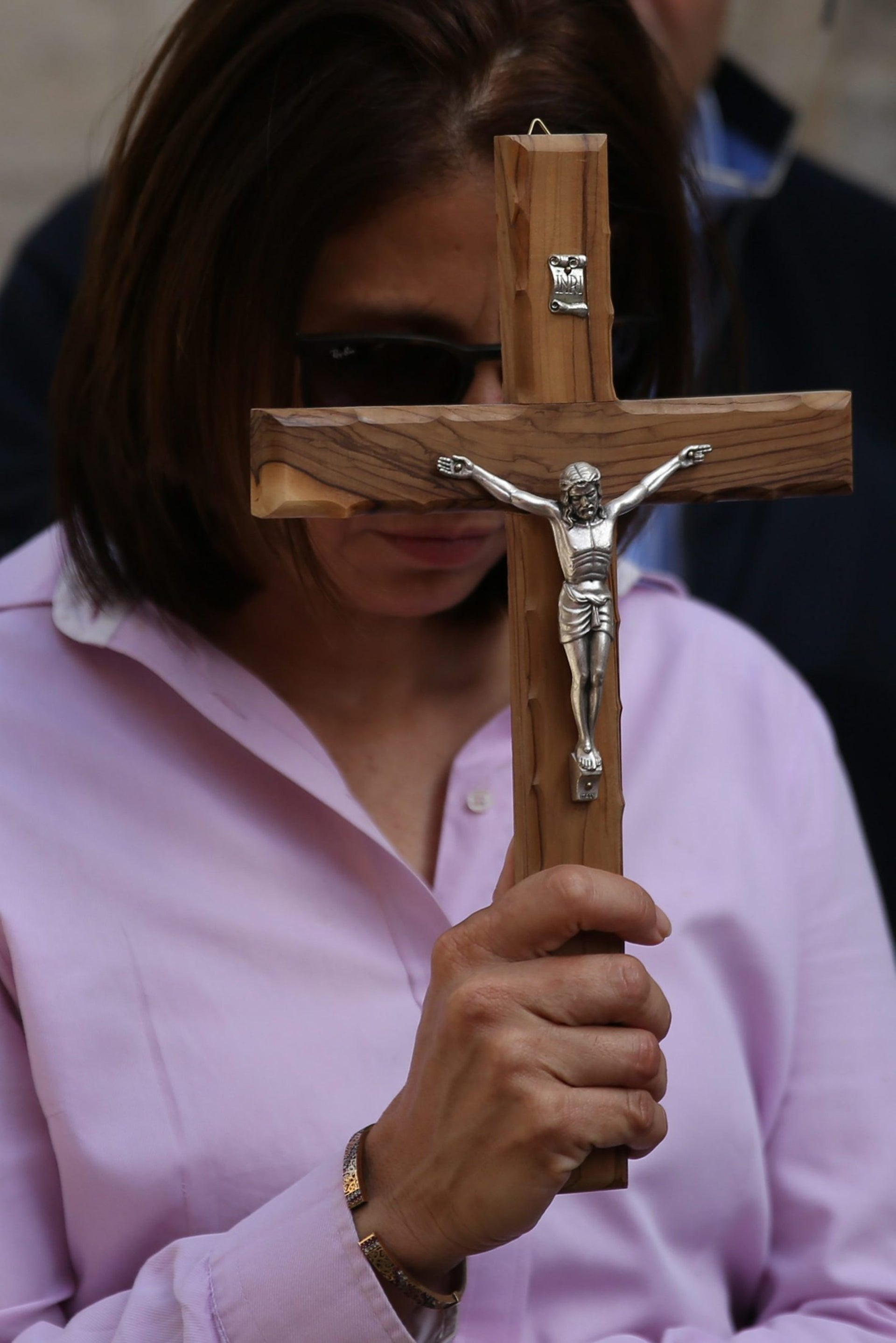 A Catholic pilgrim holds a crucifix as she prays along the Via Dolorosa (Way of Suffering) in Jerusalem's Old City during the Good Friday procession on March 25, 2016.