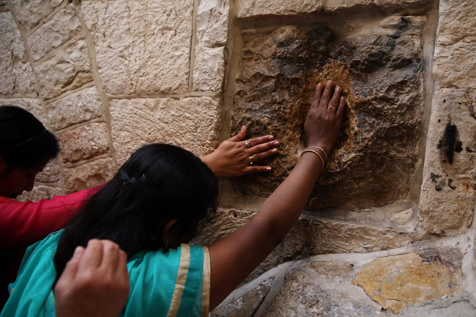 Catholic pilgrims from India pray at the 5th station of the Via Dolorosa (Way of Suffering) in Jerusalem's Old City during the Good Friday procession on March 25, 2016.