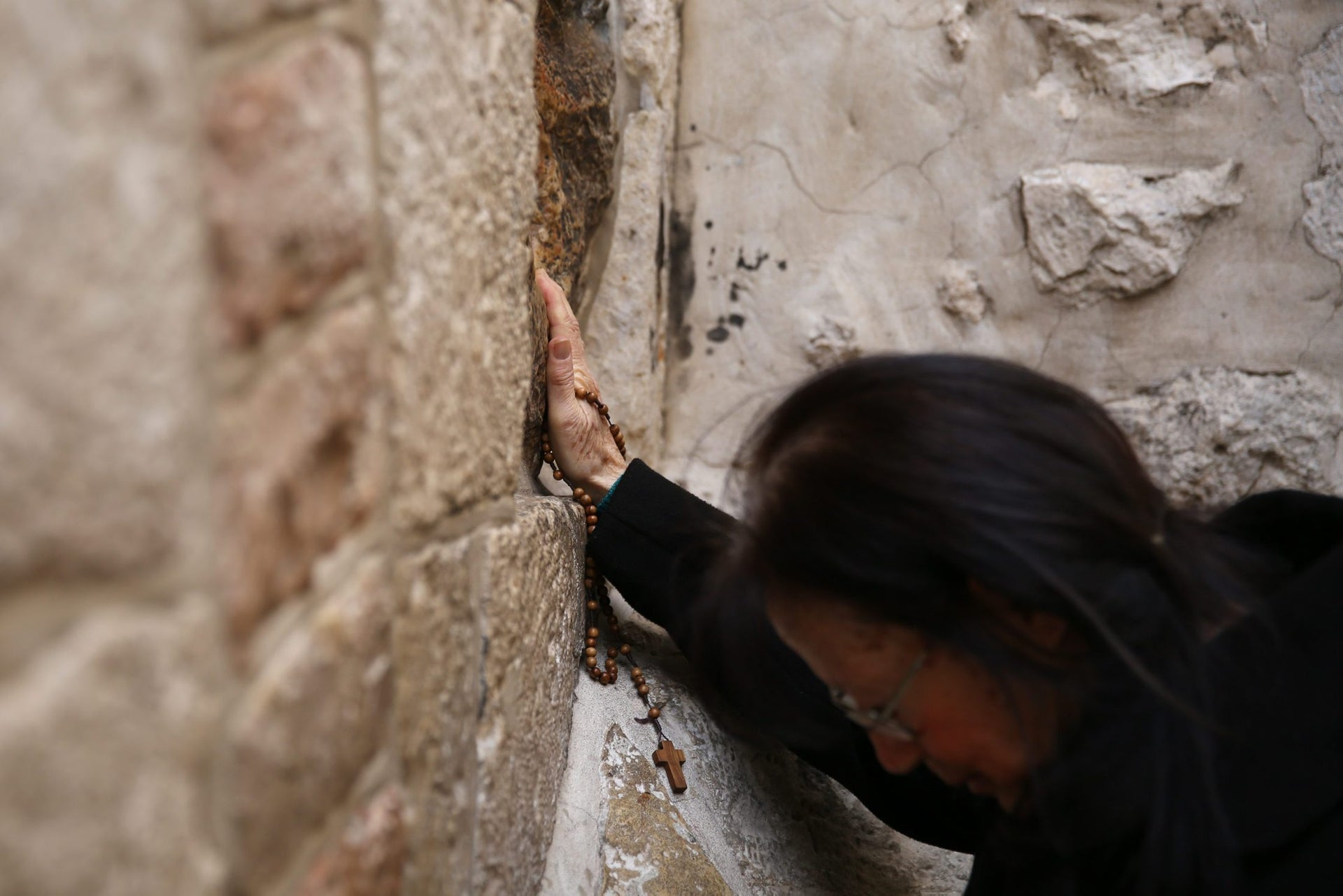 A Catholic pilgrim prays at the 5th station of the Via Dolorosa (Way of Suffering) in Jerusalem's Old City during the Good Friday procession on March 25, 2016.