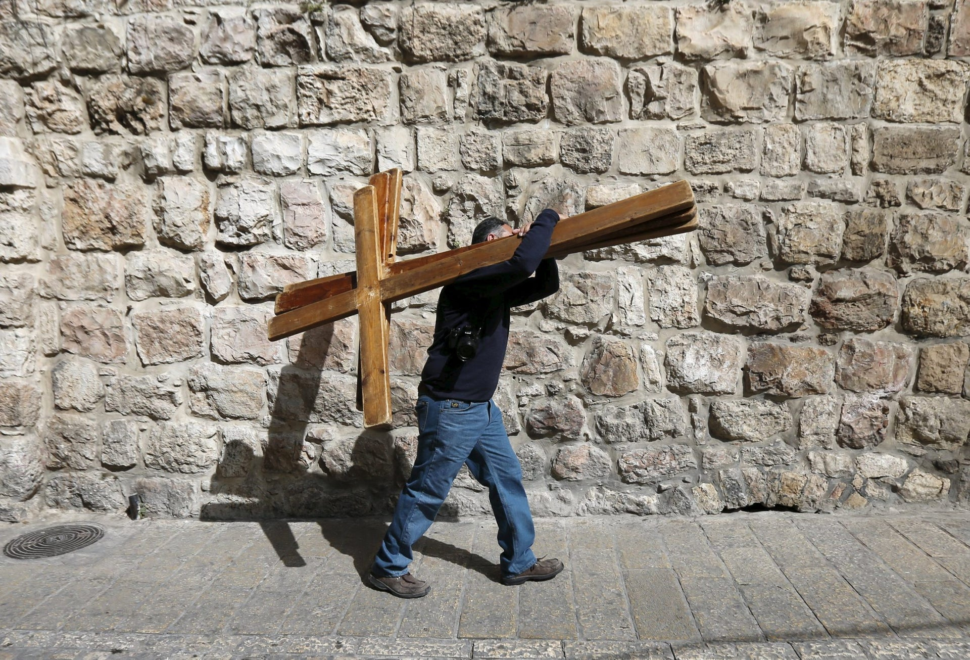 A man holds up crosses during a Good Friday procession through the Via Dolorosa in Jerusalem's Old City March 25, 2016. REUTERS/Ammar Awad